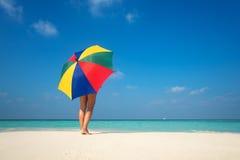 Menina com um guarda-chuva colorido no Sandy Beach Imagens de Stock