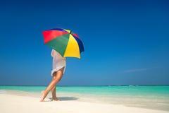 Menina com um guarda-chuva colorido no Sandy Beach Fotos de Stock