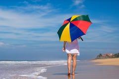 Menina com um guarda-chuva colorido no Sandy Beach Foto de Stock Royalty Free