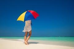 Menina com um guarda-chuva colorido no Sandy Beach Foto de Stock