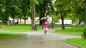 Menina com um guarda-chuva que salta em um parque vazio video estoque