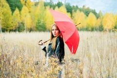 Menina com um guarda-chuva vermelho no campo em uma tarde do outono em um fundo imagens de stock