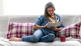 Menina com um livro e um copo em uma cama acolhedor Imagem de Stock Royalty Free