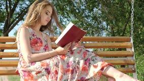 Menina com um livro em um banco no parque vídeos de arquivo