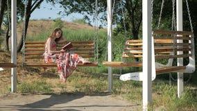Menina com um livro em um banco no parque filme