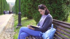 Menina com um livro em seus joelhos que lê em um banco video estoque