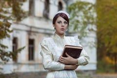 A menina com um livro no parque. Fotos de Stock Royalty Free