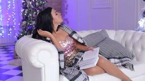 Menina com um livro no sofá perto da árvore de Natal video estoque