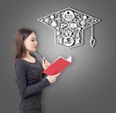 Menina com um livro vermelho e ícones da educação Foto de Stock