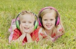 Menina com um menino nos fones de ouvido que escuta a música imagem de stock royalty free