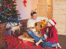 Menina com um paizinho que joga a guitarra e que canta perto do Natal tr imagens de stock