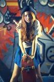 Menina com um patim com fundo urbano fotos de stock