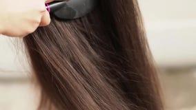Menina com um pente que penteia seu cabelo filme