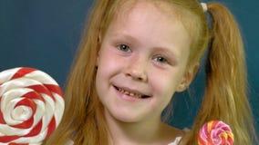 Menina com um pirulito em um fundo azul Feche acima do retrato video estoque