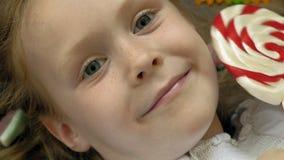 A menina com um pirulito encontra-se em um fundo azul Retrato do close up, vista superior vídeos de arquivo