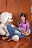 Menina com um portátil e um urso branco Imagem de Stock