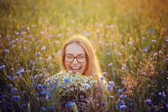 Menina com um ramalhete das margaridas e das centáureas no campo Fotos de Stock Royalty Free