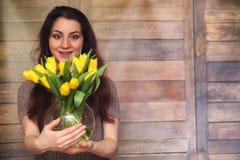 Menina com um ramalhete de tulipas amarelas Menina com um presente da flor Imagens de Stock Royalty Free