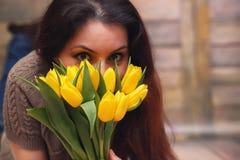 Menina com um ramalhete de tulipas amarelas Menina com um presente da flor Fotos de Stock