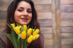 Menina com um ramalhete de tulipas amarelas Menina com um presente da flor Fotografia de Stock Royalty Free