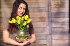 Menina com um ramalhete de tulipas amarelas Menina com um presente da flor Foto de Stock Royalty Free