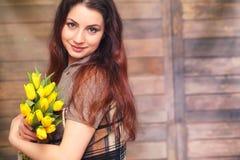 Menina com um ramalhete de tulipas amarelas Menina com um presente da flor Imagem de Stock