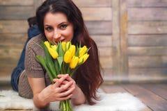 Menina com um ramalhete de tulipas amarelas Menina com um presente da flor Imagem de Stock Royalty Free