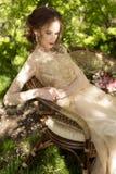 A menina com um ramalhete em um sofá fora foto de stock royalty free
