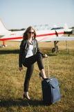 Menina com um saco azul perto dos aviões pequenos Conceito da mulher que retornou do curso no avião privado imagens de stock royalty free
