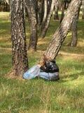 A menina com um saco de lixo pegara o lixo na floresta, proteção ambiental, controle de poluição imagens de stock royalty free