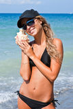 Menina com um seashell no mar. Fotografia de Stock Royalty Free
