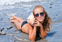 Menina com um seashell no mar. Fotos de Stock Royalty Free