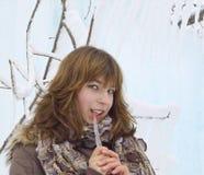 A menina com um sincelo do gelo Imagens de Stock