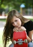 A menina com um skate foto de stock