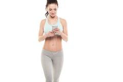 A menina com um smartphone em um fundo branco, aprecia esportes treinando, exercício da aptidão do gym Fotos de Stock Royalty Free