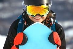 A menina com um snowboard na estância de esqui Foto de Stock Royalty Free