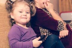 A menina com um sorriso astuto senta-se no sofá com sua mamã e joga-se um smartphone fotos de stock royalty free