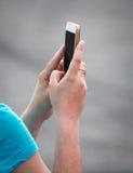 Menina com um telefone celular em sua mão Imagem de Stock Royalty Free