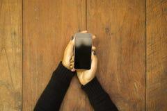 Menina com um telefone celular em um fundo de madeira Imagens de Stock Royalty Free