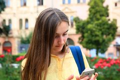 A menina com um telefone celular lê uma mensagem, Imagens de Stock Royalty Free