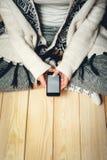 Menina com um telefone em suas mãos Foto de Stock Royalty Free
