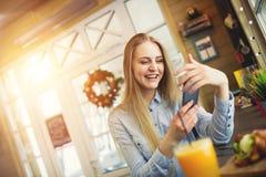 Menina com um telefone em suas mãos que descansam em um café na moda com decorações do Natal Fotografia de Stock Royalty Free