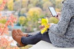 A menina com um telefone senta-se em um monte, folhas do amarelo em sua mão Aut Fotografia de Stock