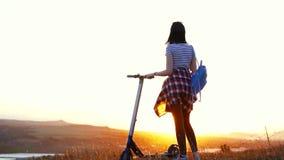 A menina com um 'trotinette' bonde está com ela para trás e olha o por do sol, mo lento vídeos de arquivo