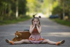 Menina com um urso da mala de viagem e de peluche que senta-se na estrada Foto de Stock Royalty Free