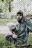 Menina com um urso de peluche atrás da cerca imagem de stock