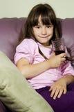 A menina com um vidro do suco em um sofá Imagens de Stock Royalty Free