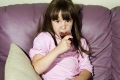 A menina com um vidro do suco em um sofá Fotos de Stock Royalty Free