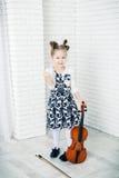 A menina com um violino ameaça o punho fotos de stock