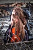 Menina com um violino que senta-se nas cinzas fotografia de stock royalty free